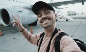 Influencer Marketing: Male Influencer smiling in front of airplane